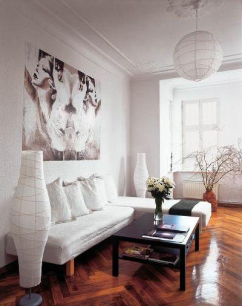 W salonie dużo bieli i kontrastujący czarny stolik.