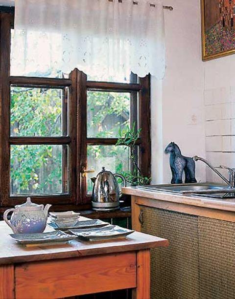 Kuchenne szafki Budzowscy zrobili sami. Drzwiczki ozdobione słomianą matą doskonale pasują do wiejskiej kuchni.