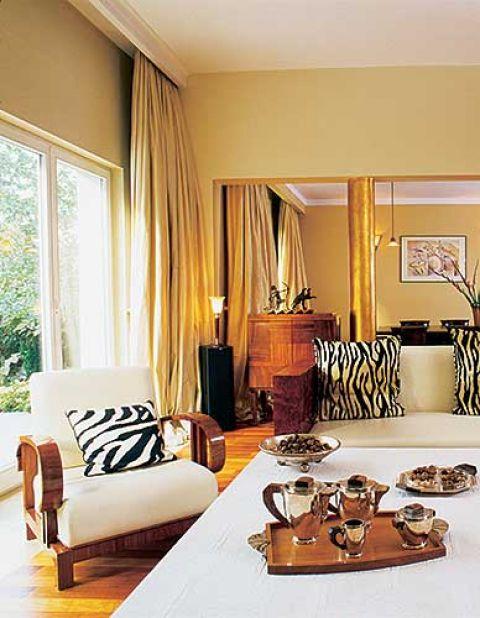 Pokryta platkami złota kolumna współgra z barwą zasłon, a paski zebry - ulubiony wzór artdekowskich tkanin - kontrastują z