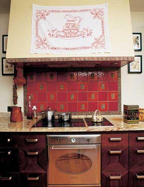 Kafle nad piecem Iwona wymyśliła sama. Czerwień ze złotymi wzorami symbolizuje ciepło domowego ogniska.