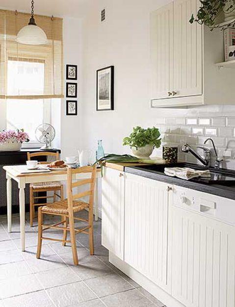 W kuchni drewniany stół z białymi nogami.