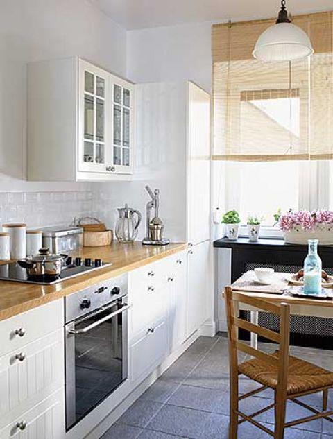 W jasnej kuchni są białe szafki. Dyskretny urok czerwieni