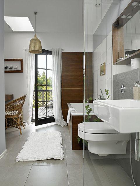 Łazienka z tarasem i zieloną ścianką z panących się po drutach bluszczy Hedera Helix.