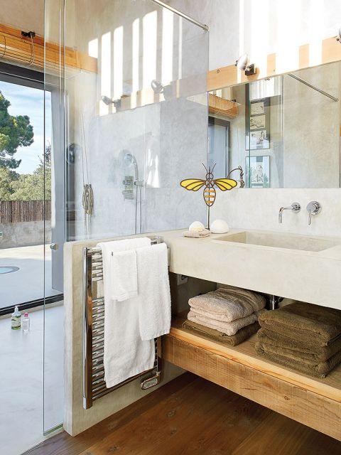 W łazience ciekawe zestawienie betonowych, szarych ścian z ciepłym drewnem, z którego wykonano półkę pod umywalką.