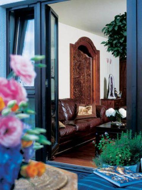 Indonezyjskie rzeźbione drzwi prowadzą z salonu do kuchni.