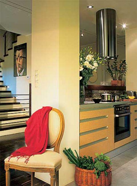 Geometryczne formy schodow i kuchennych szafek ocieplają kolorowe dodatki.