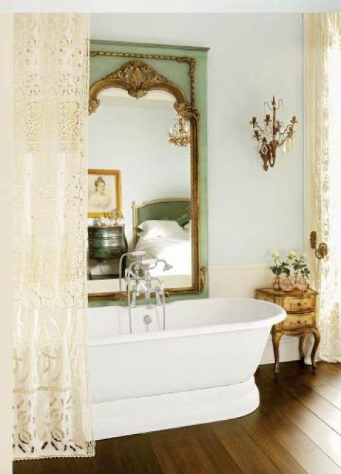 Romantyczna łazienka z koronkową zasłoną. W ogromynym weneckim lustrze odbija się Biała sypialnia.