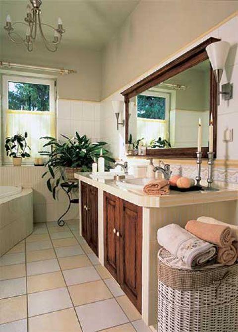 Nad umywalkami wisi lustro w drewnianej ramie.