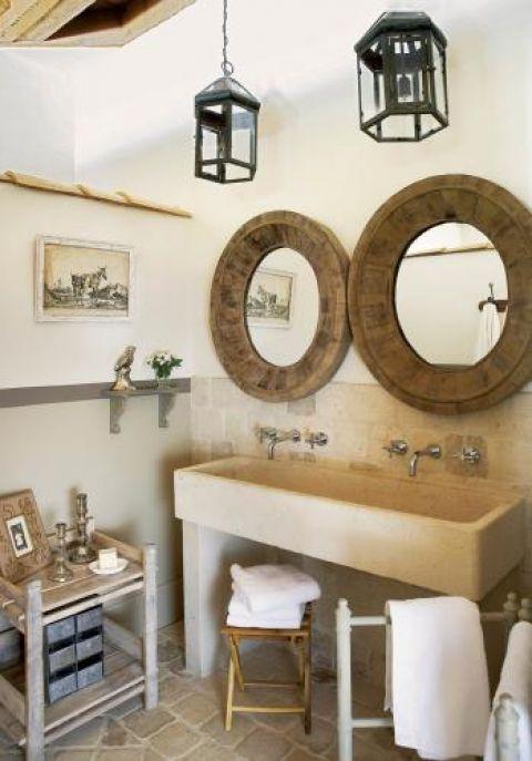 Kamienna podłoga i umywalka komponują się z drewnianymi ramami luster i lampionami.