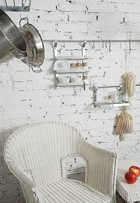 Do bielonych cegieł w kuchni gospodarze dopasowali wiklinowe meble.
