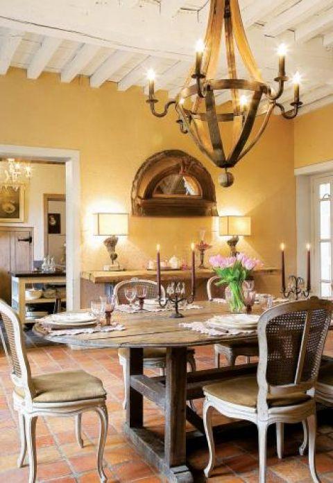 Prosty drewniany stół i zdobione krzesła.