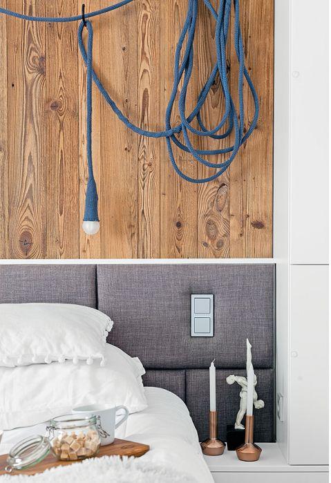 Na ścianie szarej sypialni w stylu skandynawskim jest wiekowe drewno.