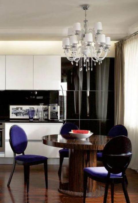Przy ciemnym drewnie, bieli i szarości ścian oraz czarnych meblach fioletowe obicia foteli wyglądają intrygująco.