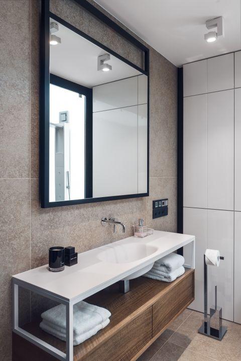 Luksusowa łazienka jest urządzona minimalistycznie. Proste kształty, jasne kolory, ciekawe połączenia faktur.