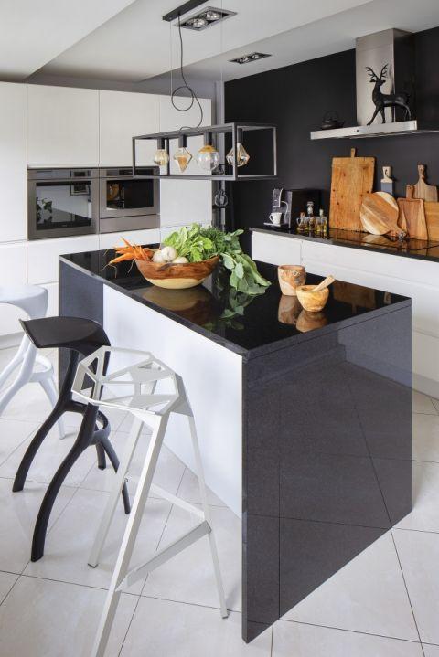 Nowoczesnej biało-czarnej kuchni przytulności dodaje drewno: misy, moździerze i deski do krojenia.