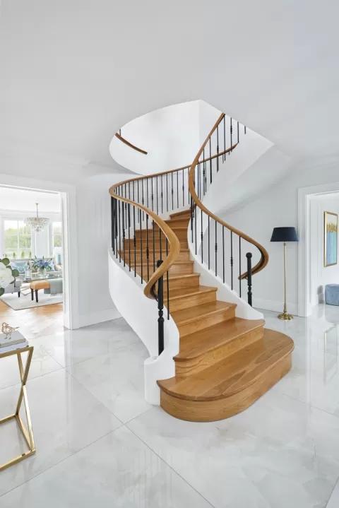 biały hol klasyczny z drewnianymi schodami