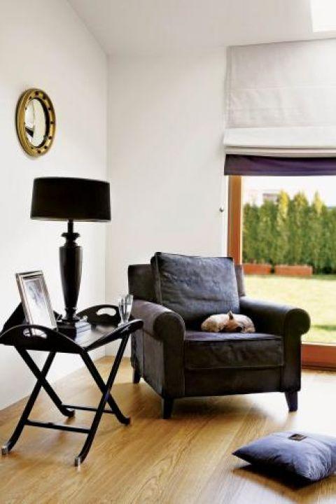 Czarny fotel przyjechał z targów meblowych w Portugalii, a stolik- z angielskiej wypożyczalni mebli.