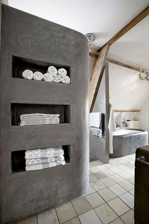 Drewniane wsporniki sufitu w surowo urządzonej łazience.