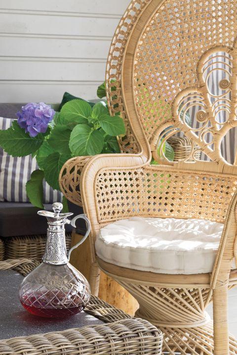 Królem foteli na werandzie jest finezyjnie pleciony paw, kupiony na Westwingu. Letni salon w południe
