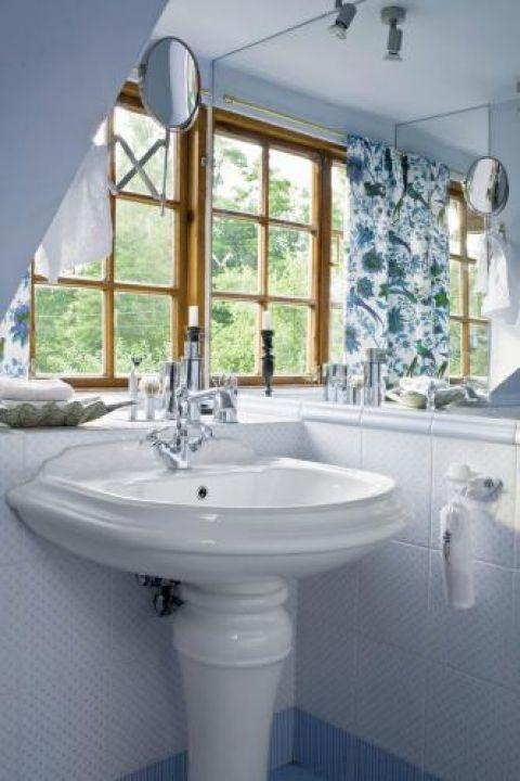 Jasna łazienka z dekoracyjnymi zasłonami.