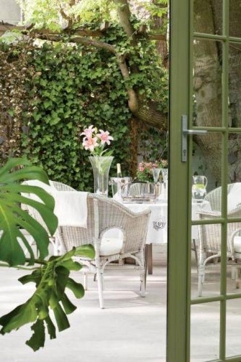 Jasna posadzka i białe meble ogrodowe pięknie komponują się z intensywną zielenią.