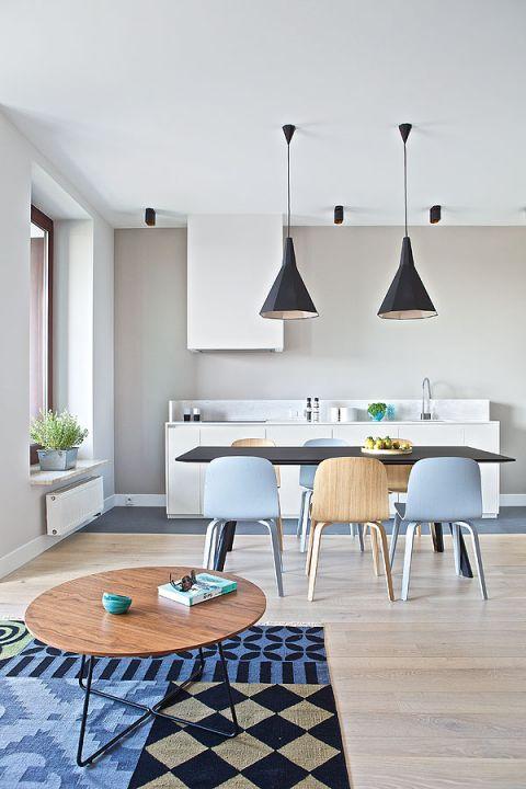 Kuchnia urządzona na biało, ale ciepły ton nadają jej nowoczesne krzesła w kolorze naturalnego drewna i gołębiego błękitu.