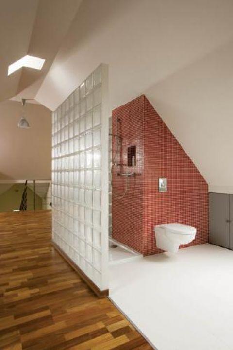 Łazienka oddzielona ścianą z luksferów.