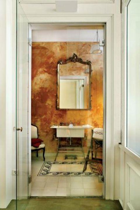 Łazienkę od sypialni oddzielają wysokie szklane drzwi. Stiuk, mozaika, francuskie lustro, stary fotel, biblioteczne schodki