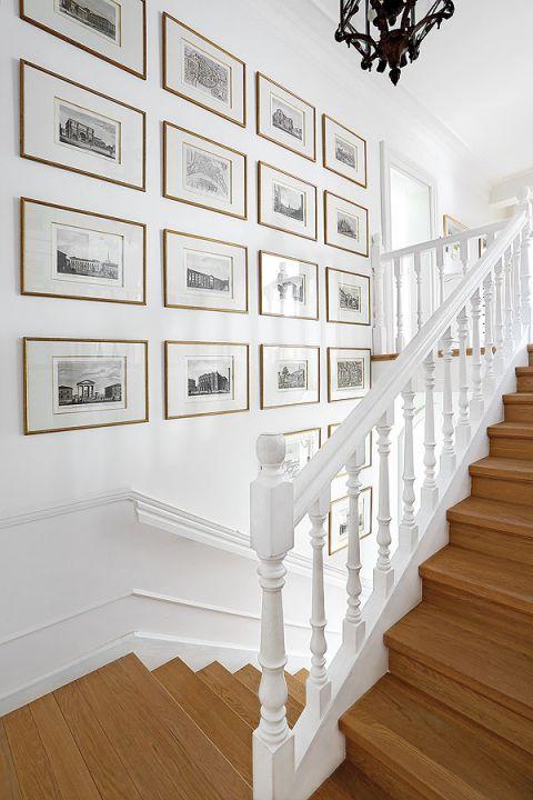 Na ścianie przy schodach symetrycznie powieszone obrazy.