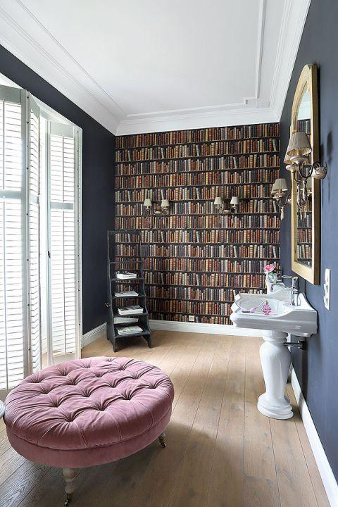 Niczym pokój - z wygodną puffą i ścianą książek - tapetą imitującą okaźną bibliotekę.