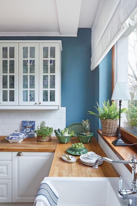 niebieska kuchnia z białymi szafkami i drewnianym blatem