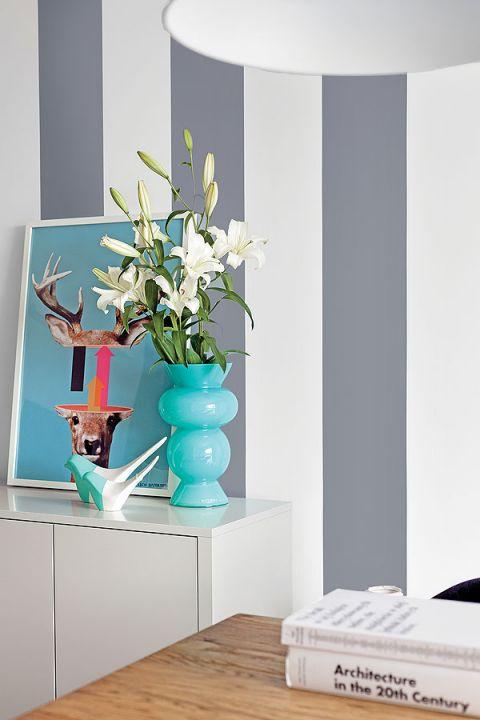 Ściana w malowane pasy. Obraz z jelonkiem i łanią na vespie, namalowany przez Lecha Batora.