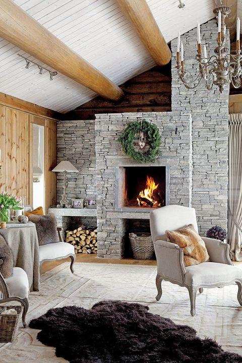 Surowe ściany z drewna i szary, kamienny kominek podgrzano finezyjnym detalem.