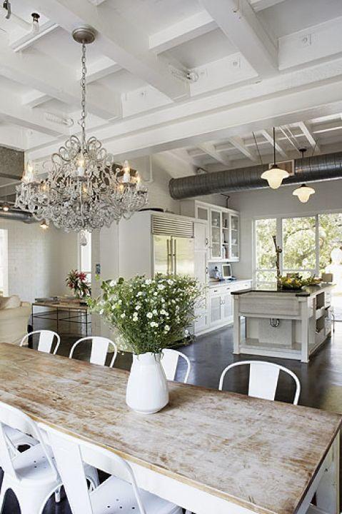 Swojskie kwiaty na tle kuchni, która wygląda jak w loftach.