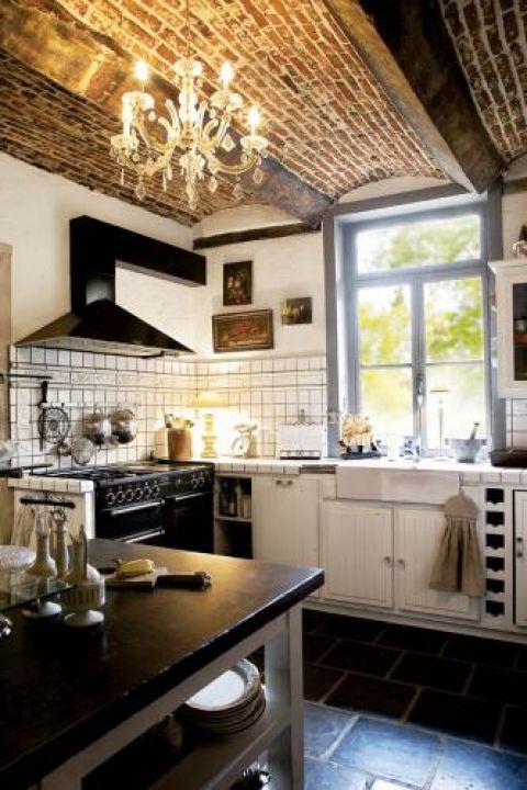 W kuchni wenecki żyrandol na tle ceglanego sufitu, superpiecyk La Cornue i stół z bazaltowym blatem. Do tego dużo