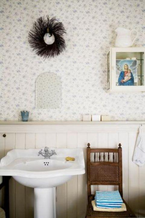 W łazience gospodyni zrezygnowała z ceramicznych płytek i zastąpiła je drewnianymi panelami oraz tapetą.