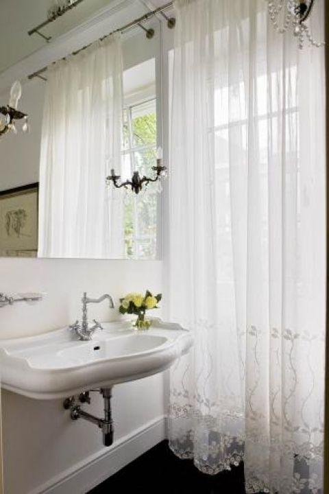 Wszystko biale. Zdobiona koronką firanka i stylizowana umywalka - po prostu kobieco.