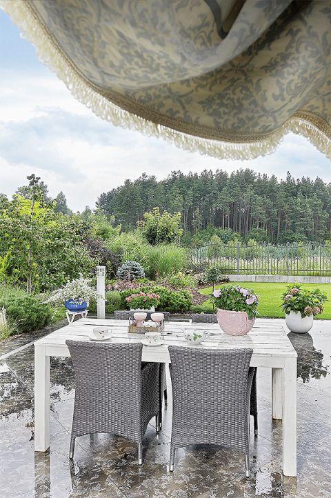 Urządzony naturalnie, sielsko: stół, plecione fotele, kwiaty.