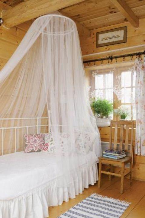 W gościnnej sypialni też czuć dotyk kobiecej ręki- koronkowe firanki, kwieciste poduszki i świeże kwiaty na parapecie.