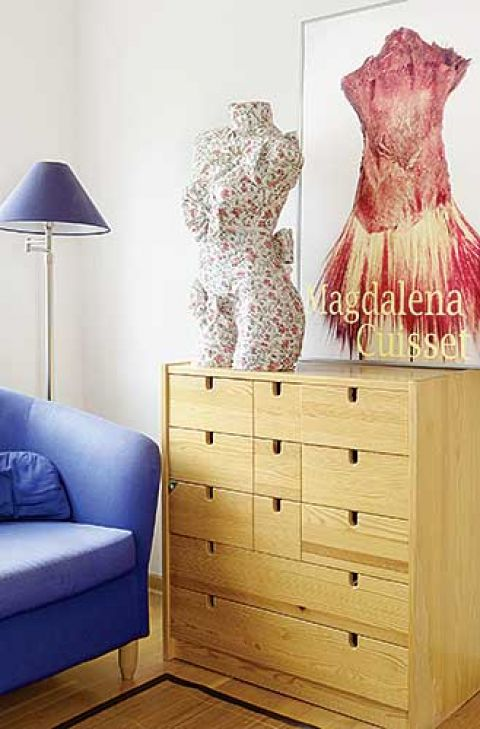Na komodzie stoi ubrany manekin. Kobieta i lampy