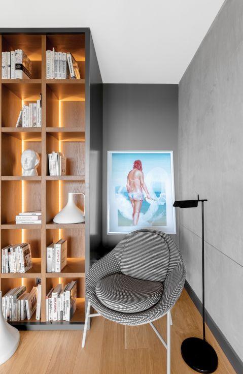 Podświetlona biblioteka nie tylko ładnie wygląda, sprawia też, że w lofcie robi się przytulniej. Fotel