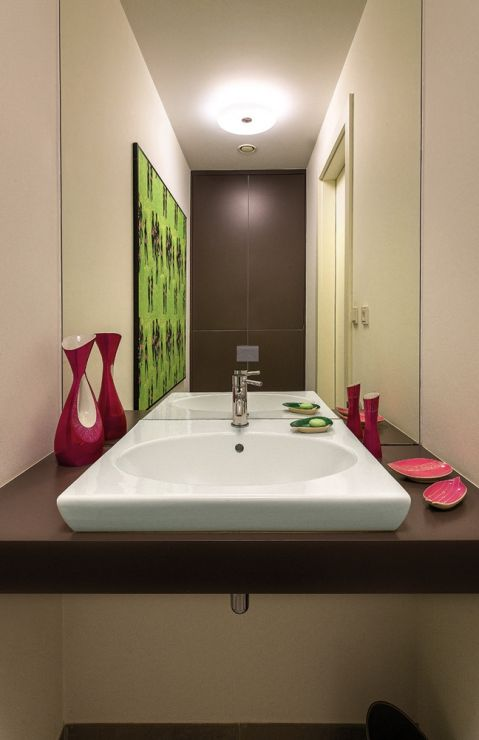 W toalecie gościnnej porcelana z Chodzieży i Ćmielowa, wzory z lat 60. oraz oprawiona w ramy kolorowa tkanina Łaźnia