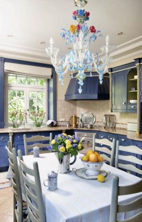 Niebieskie szafki nadają kuchni ciepła.