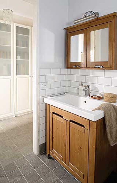 Z jasnym wystrojem łazienki kontrastują drewniane szafki.