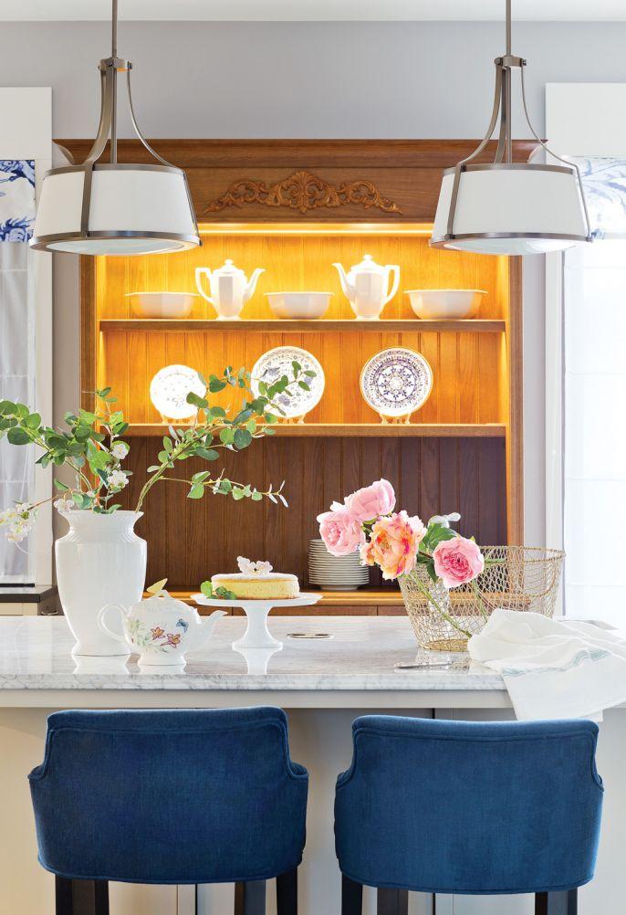 Podświetloną witrynę zrobiła na zamówienie (tak jak pozostałe meble w zabudowie) Justolarnia – BartŁomiej Pieniaszek. Pluszowe krzesła Chesterfield i niebieską kuchenkę Stoves dobrano pod kolor kolekcji porcelany.