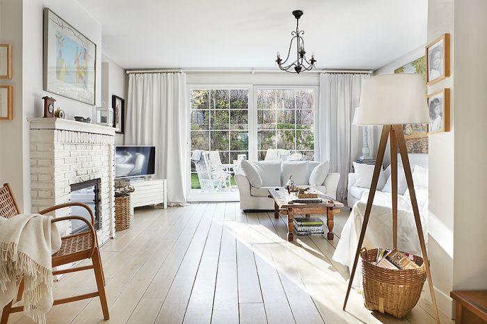 Salon w bieli. Zamiast marmuru wokół kominka cegła i drewniane decha pomalowana na biało.