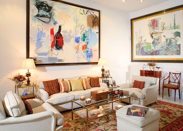 W salonie jasna kanapa i fotele oraz szklany stolik.
