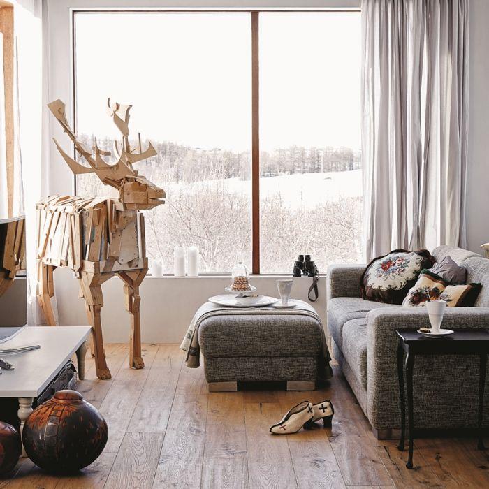 Stalowe szafki wydają się mniej chłodne w zestawieniu z ciepłymi deskami na podłodze. Ogromne okna