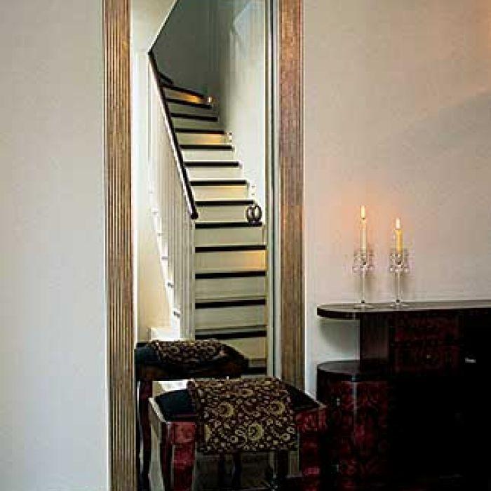 Dwa w jednym - drzwi do garderoby i lustro, w którym malowniczo odbijają się schody. Po przesunięciu szklanej tafli
