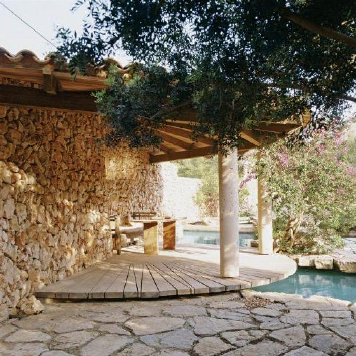 Na tarasie dominuje jasny kamień i surowe drewno.